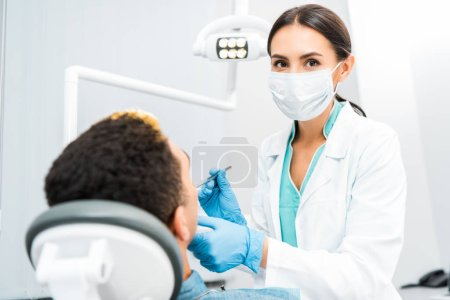 Photo for Female dentist in latex gloves and mask examining african american patient - Royalty Free Image