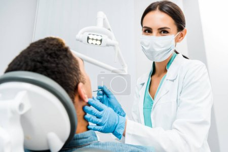 Photo for Female stomatologist  in latex gloves and mask examining african american patient - Royalty Free Image