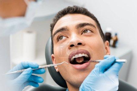 Afrikanisch-amerikanischer Mann mit offenem Mund bei Untersuchung in Zahnklinik