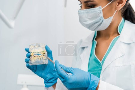 female stomatologist in mask showing dental jaw model with braces