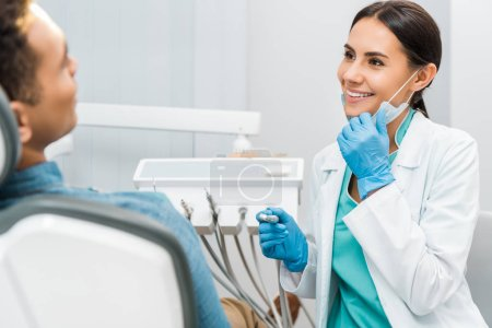 cheerful female dentist holding mask and drill and smiling near patient