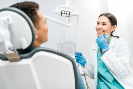 smiling female dentist holding drill near patient