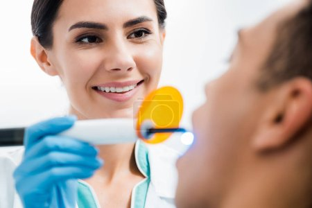selective focus of female dentist making bleaching procedure to african american patient