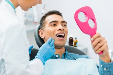 female dentist holding medical instrument near african american patient looking at mirror