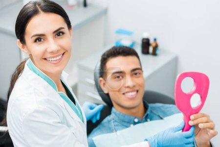 selektiver Fokus attraktiver Zahnärztin, die in der Nähe einer afrikanisch-amerikanischen Patientin steht
