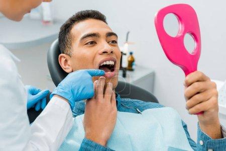 Photo pour Dentiste femme toucher la dent du bel homme afro-américain regardant miroir - image libre de droit