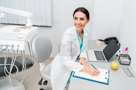 Photo pour Attrayant femme médecin, prendre des notes près de portable - image libre de droit