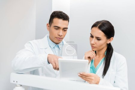Photo for Serious multiethnic doctors looking at digital tablet - Royalty Free Image