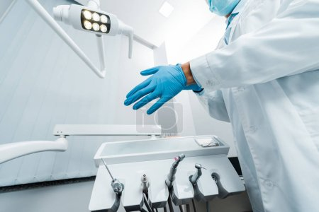 cropped view of male dentist wearing latex glove