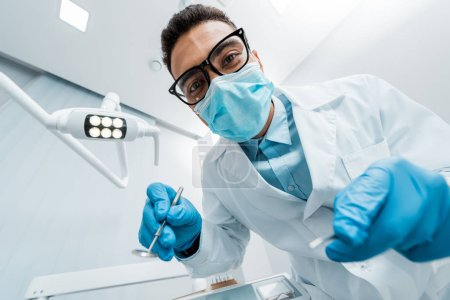 Photo for African american stomatologist in glasses and mask with dental instruments in hands - Royalty Free Image