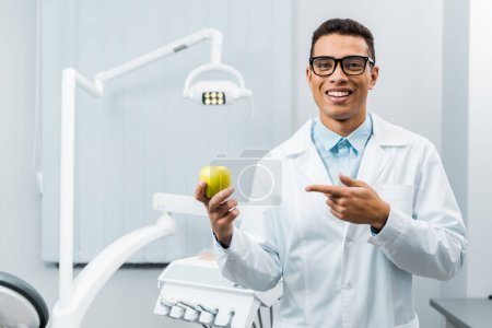 Photo for Handsome african american doctor in glasses pointing at apple - Royalty Free Image