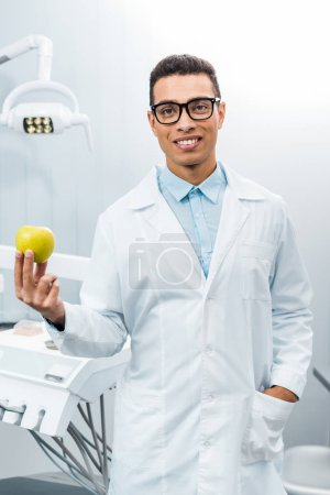 Photo for Handsome african american dentist with hand in pocket holding apple - Royalty Free Image