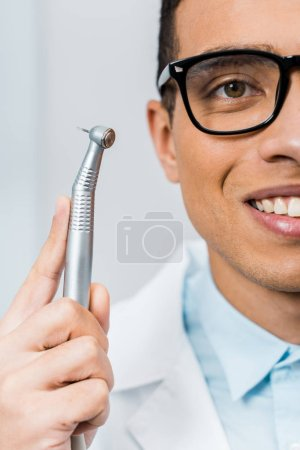 Photo for Close up of smiling african american dentist in glasses holding drill - Royalty Free Image