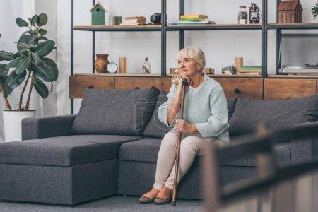 Foto de Mujer senior ensueño sentado en el sofá con poca caña en sala de estar - Imagen libre de derechos