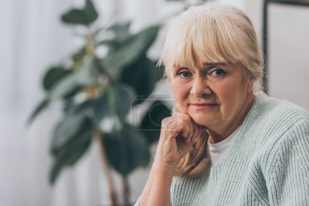 sad retired woman with blonde hair at home