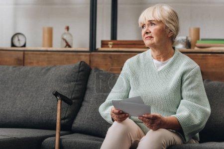 bouleversé la retraite femme avec des cheveux blonds, tenant des vieilles photos tout en étant assis sur le canapé
