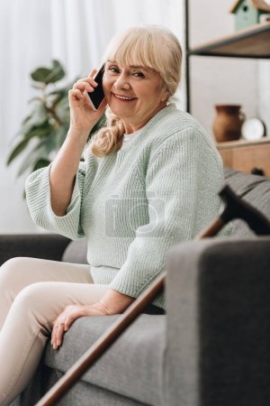Foto de Mujer senior alegre hablando en teléfono inteligente mientras está sentado en el sofá - Imagen libre de derechos