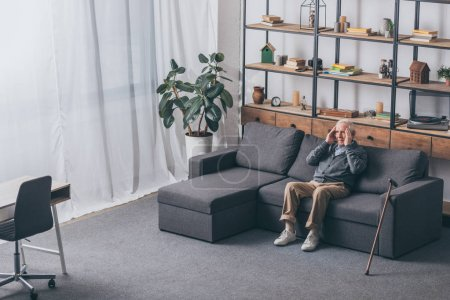 Photo for Senior man with grey hair having headache while sitting on sofa - Royalty Free Image