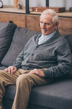 Photo for Sad senior man with grey hair sitting on sofa - Royalty Free Image
