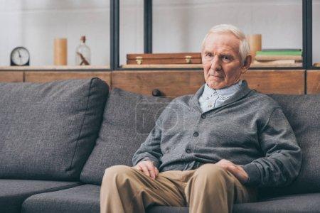 Photo pour Homme retraité bouleversé avec les cheveux gris assis sur le canapé - image libre de droit
