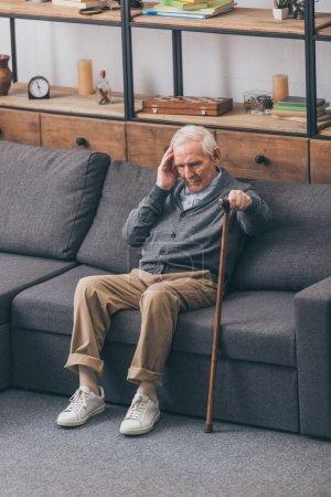 Foto de Hombre jubilado con cabellos grises con dolor de cabeza mientras está sentado en el sofá - Imagen libre de derechos