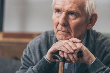 close up of retired man with grey hair holding walking cane