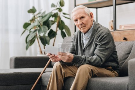 Photo for Upset pensioner with grey hair holding photos while sitting on sofa - Royalty Free Image