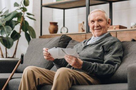 cheerful senior man with grey hair holding photos and sitting on sofa