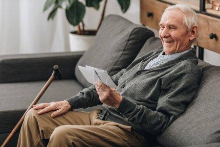 Photo pour Heureuse retraité avec des cheveux gris regarder des photos et assis sur le canapé - image libre de droit