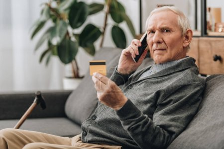 Photo for Senior man talking on smartphone and holding credit card - Royalty Free Image