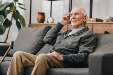 thoughtful senior man with grey hair sitting on sofa in living room