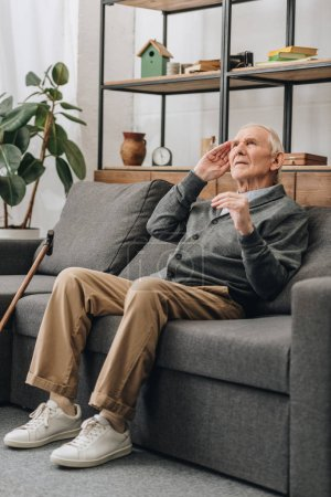 Photo for Dreamy senior man with grey hair sitting on sofa in living room - Royalty Free Image