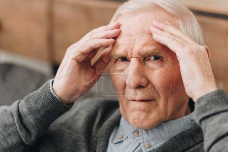 Foto de Hombre jubilado sosteniendo la cabeza teniendo dolor de cabeza - Imagen libre de derechos