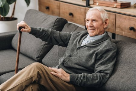 smiling retired man sitting on sofa with walking cane