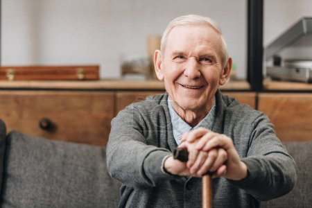 Photo for Cheerful pensioner smiling and holding walking cane at home - Royalty Free Image