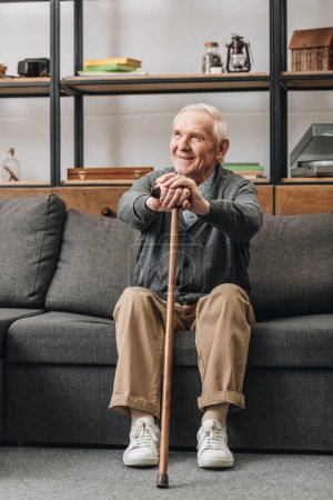 cheerful pensioner smiling and holding walking stick and sitting on sofa