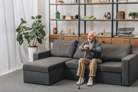Photo for Happy senior man smiling and holding walking cane while sitting on sofa - Royalty Free Image