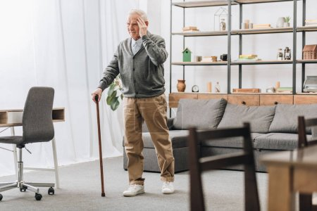 Photo for Senior man standing with walking cane while having headache - Royalty Free Image