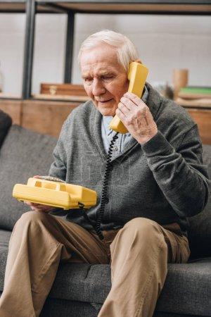 Foto de Hombre jubilado usando teléfono viejo sentado en el sofá - Imagen libre de derechos