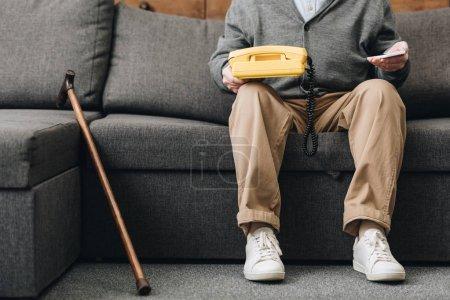 Photo pour Vue recadrée de retraite homme tenant des smartphone et téléphone rétro tout en étant assis sur le canapé - image libre de droit