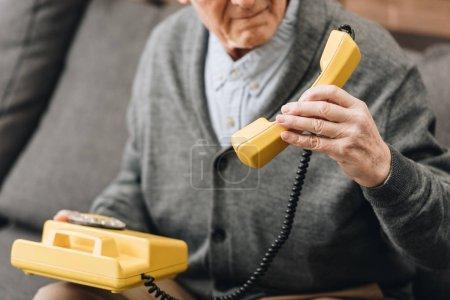 Foto de Recortada la visión del hombre senior sosteniendo teléfono retro en casa - Imagen libre de derechos