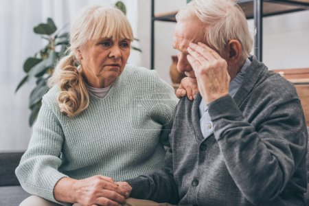 Photo for Retired woman holding hands with senior husband having headache - Royalty Free Image