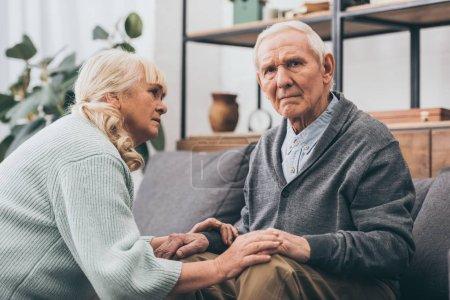 Foto de Jubilada esposa mirando marido senior en sala de estar - Imagen libre de derechos