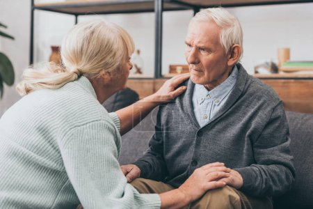 Photo for Retired couple holding hands and looking at each other at home - Royalty Free Image