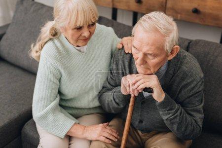soutien femme senior, assis près de triste retira mari avec la canne de marche