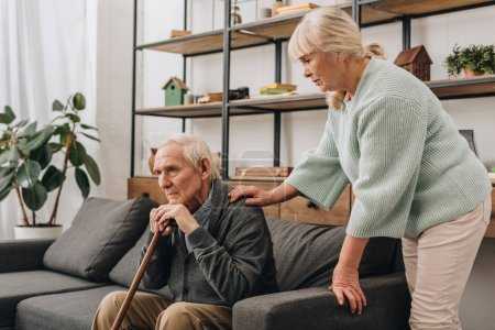 senior wife standing near retired husband sitting on sofa