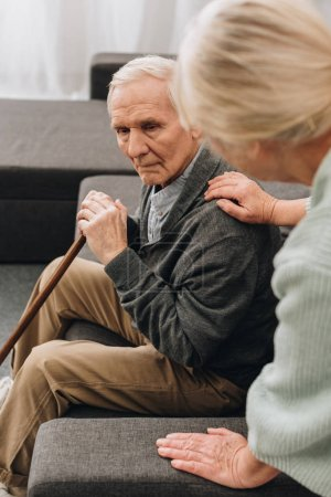 sad retired husband with walking cane sitting in living room near senior wife