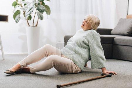 senior woman with blonde hair sitting on floor near sofa