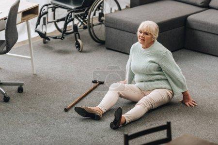 helpless senior woman with blonde hair sitting on floor near sofa and wheelchair