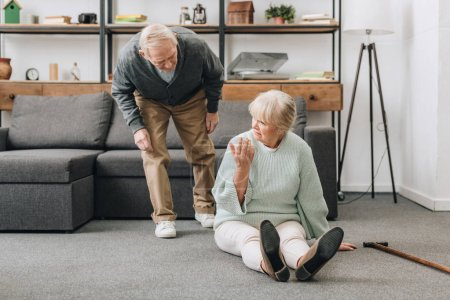 retired husband coming to upset senior wife sitting on floor with walking cane